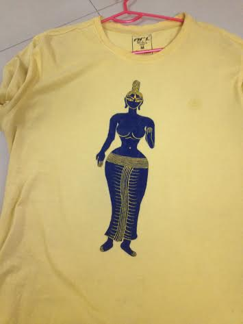 A tall lady buddha figurine in blue on the yellow T-shirt